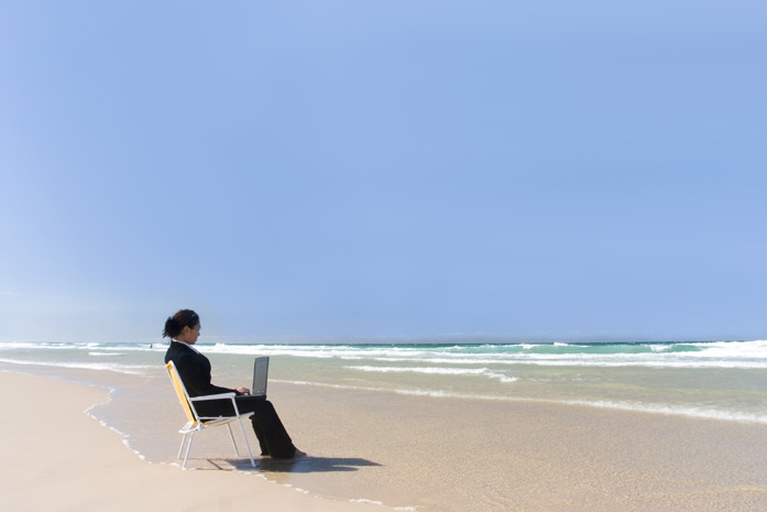 Businesswoman working on the beach with her laptop