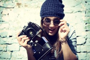 Girl has fun with vintage photo camera outdoor