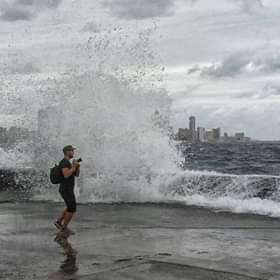 Photographer Marco Cirone with his camera while shooting in front of the sea