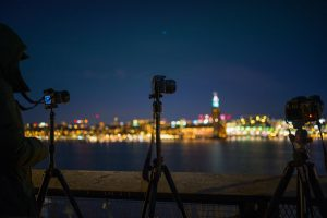 Reflex cameras on tripods while shooting a time-lapse in a city at night